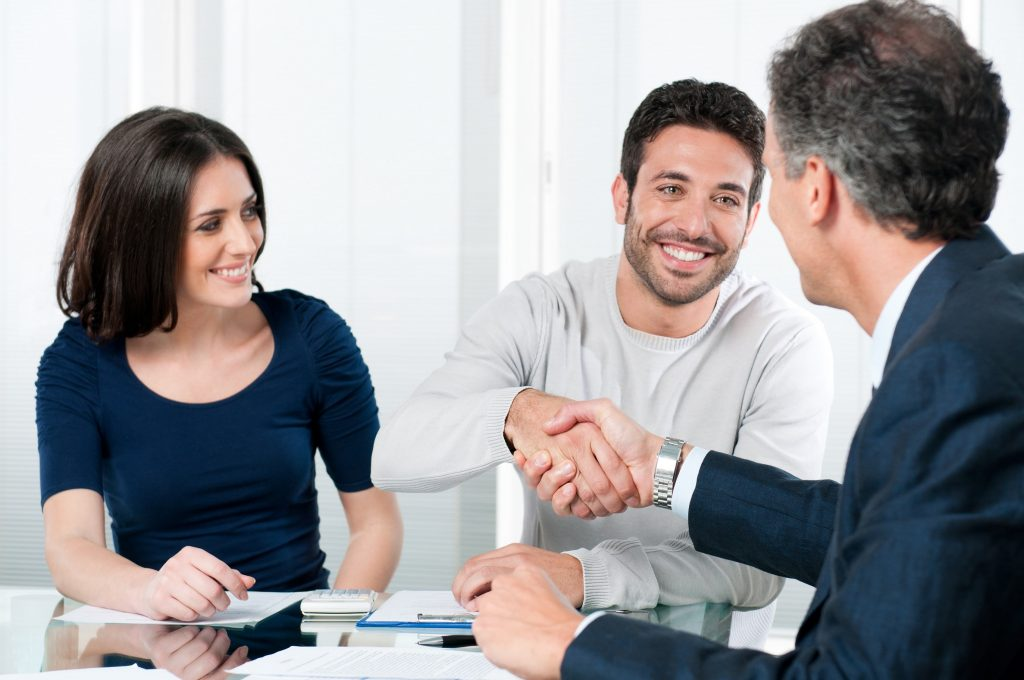 Happy couple seal a deal with their personal financial advisor at home.