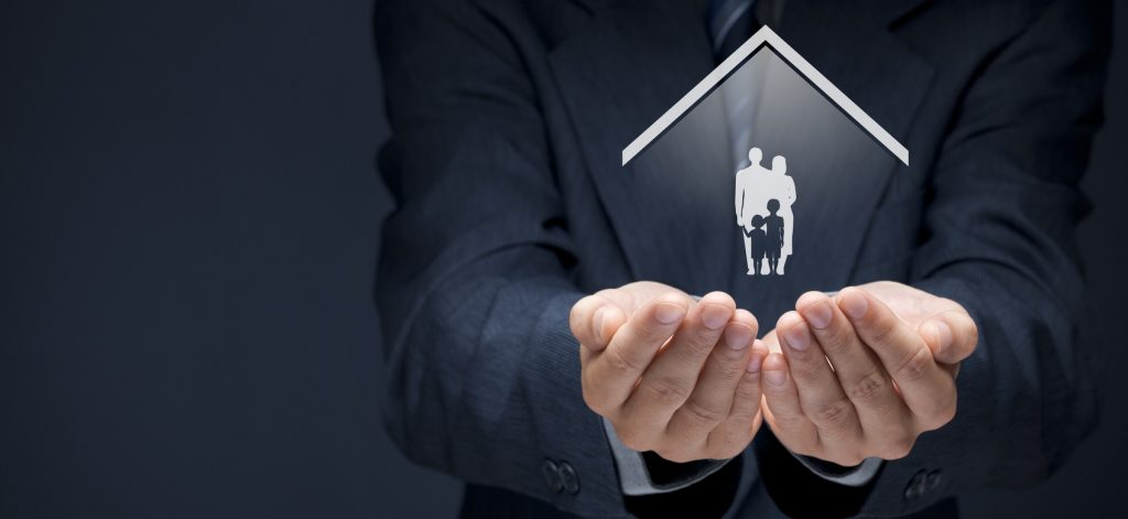 Insurance concept of family life and property insurance, family services, family policy and supporting families concepts. Businessman with protective gesture and silhouette representing young family and house.